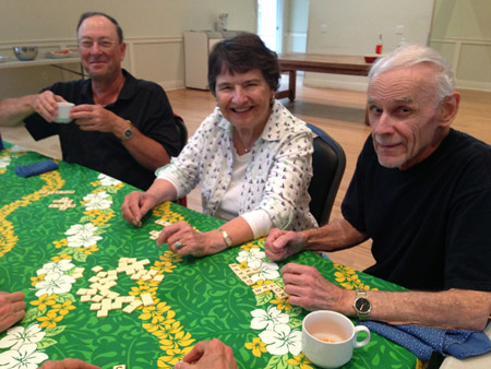 Three adults playing bananagrams