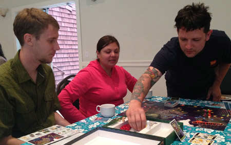 Eric, Reena, and Mugsy play a hot game of Pandemic