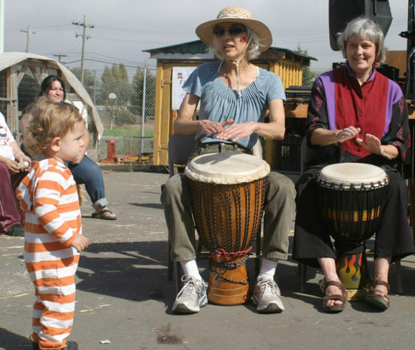 Toddler enthralled by music by Rhythmix drummers.